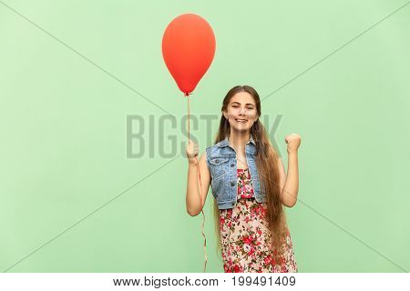 Its winn! The beautiful blonde teenager with red balloons on a green background. Isolated studio shot