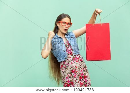 The happyness beautiful long haired girl in casual clothing with shopping bags looking at camera celebrates the victory. Caucasian blondie model. Sales shop retail consumer concept. Isolated studio shot on light blue background