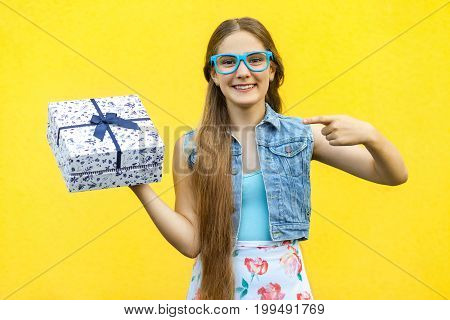 The beautiful smiling girl in dress and blue glasses pointing finger on present box and toothy smile isolated over yellow background. Indoor studio shoot