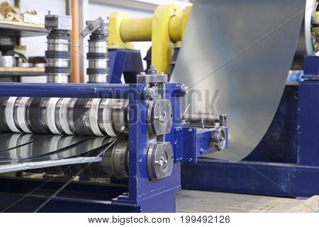 Process of cutting a wide sheet of metal into narrow strips on a machine Russia
