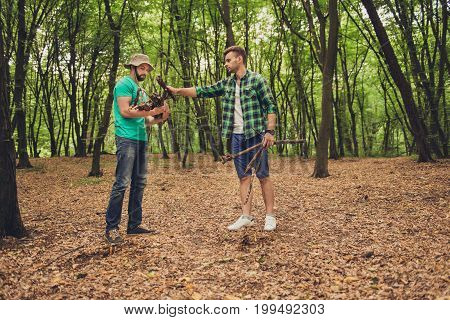 Two young male tourists in the wood in fall collecting wood for a camp fire for barbeque helping each other team work