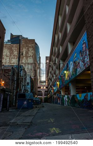 Downtown Phoenix side alley with colorful artwork reflecting the morning light on August 11, 2017.  Trash dumpsters line the opposite side.