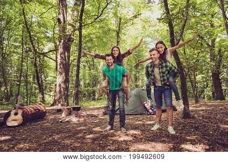 Chill fun joy love and friendship! Four friends are fooling around in a wood at a campground boys piggyback their ladies