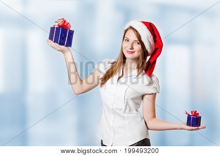 Woman in Santa Claus hat chooses large or small gift