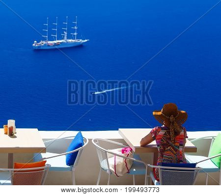 Woman in hat sitting in cafe and enjoys views of the Caldera and cruise ship, Santorini, Greece
