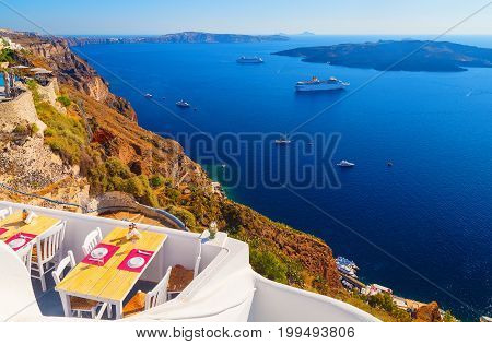Hotel in Fira on the cafe overlooking the Caldera and cruise ship at sea. Santorini, Greece