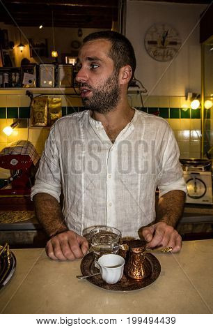 MOSTAR, BOSNIA AND HERZEGOVINA - AUGUST11, 2017: Barista in traditional Bosnian coffe shop in Mostar