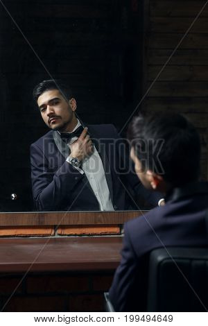 Man In Blue Suit And Butterfly Sitting In Chair Looking In The Mirror In Barbershop