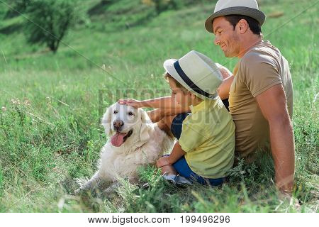 Good dog. Joyful boy is encouraging his dog while touching his forehead gently. Father is sitting near them on grass and smiling. Family is wearing cool hats