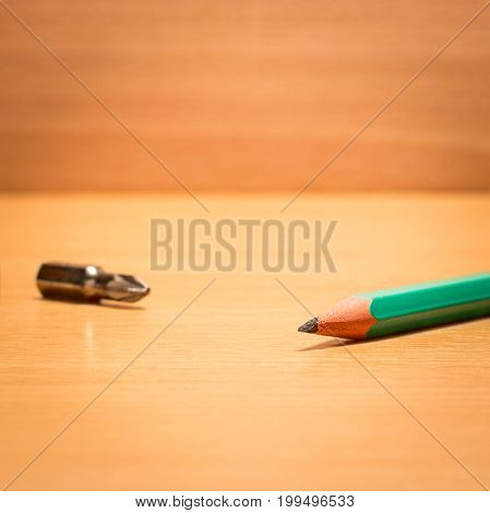 Simple pencil and screwdriver on a wooden background tools for various projects