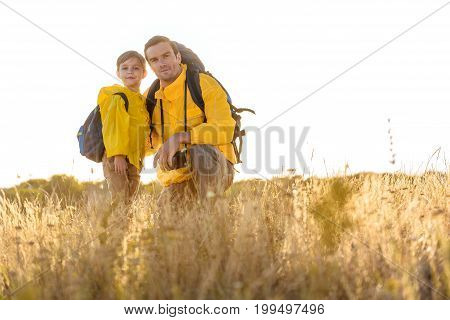 Enjoying journey together. Low angle portrait of happy man embracing his son while kneeling on grass. He is wearing yellow raincoat and backpack. Copy space
