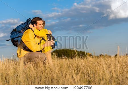 Enjoying travel with family. Happy father is hugging his son with love and smiling. He is kneeling on wheat field while carrying backpack. Copy space in right side