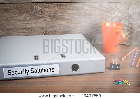 Security Solutions. Folder, Coffee Mug and colored pencils on wooden office desk.
