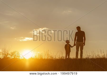 Full length portrait of happy father and son standing on meadow with relaxation. They are holding hands and looking at each other with love. Sunset on background