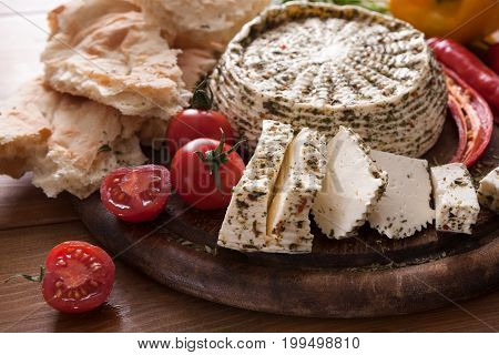 Homemade indian soft cheese paneer with herbs on wooden board with fresh vegetables and bread, side view