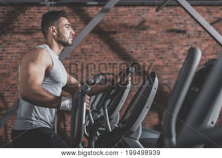 Side view profile bearded man expressing seriousness while going in for sport in modern exercise room. Copy space