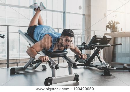 Portrait of bearded athlete expressing seriousness while taking exercise with special fitness machine in keep-fit studio