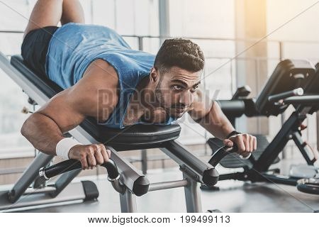 Portrait of unshaven man showing calmness while going in for sports in comfortable apartment
