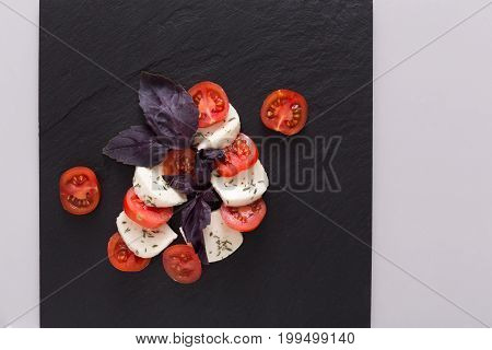 Mozzarella on black stone plate, isolated on white background, top view. Homemade fresh cheese with tomato and basil, italian cuisine