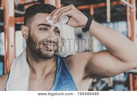 Young bearded athlete demonstrating happiness while wiping sweat on forehead by towel in gym