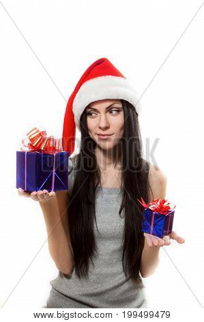 Girl in Santa Claus hat chooses large or small gift