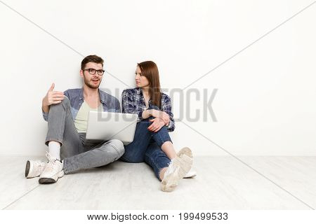 Couple conversation with laptop. Man and woman watching movie on laptop computer abd discuss it, white background, studio shot