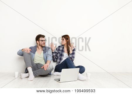 Couple discuss something unpleasant with laptop next to them. Man and woman sitting on the floor in white interior of their new apartment