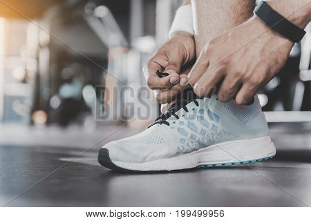 Close up male arms lacing new modern shoes for practicing exercise in keep-fit studio