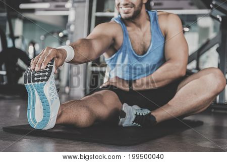 Close up man foot wearing new trainers. Outgoing unshaven male working out in keep-fit studio