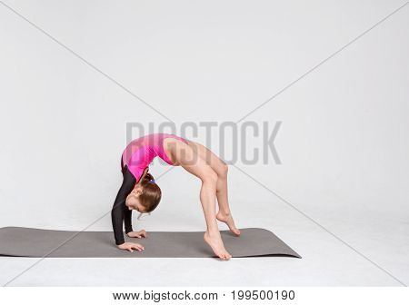Little girl gymnast in leotard at white studio background. Sporty child doing back stretching exercises. Healthy and active childhood concept, vertical, copy space