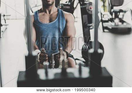 Focus on close up man arms doing multiple competition builder of back in keep-fit studio