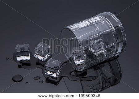 A studio image of a tipped over glass with spilled water and ice.