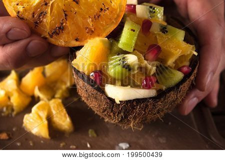 Close up picture of tropical fruit salad in coconut shell. Orange, apple, kiwifruit pieces in nut bowl and pomegranate decoration