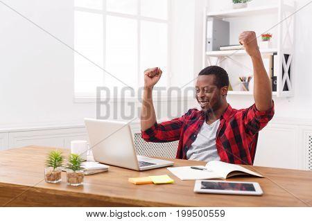 Happy businessman celebrate, win. Winner, black man in office with laptop