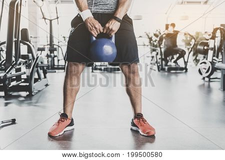 Focus on close up legs of man practicing with kettlebell in keep-fit studio