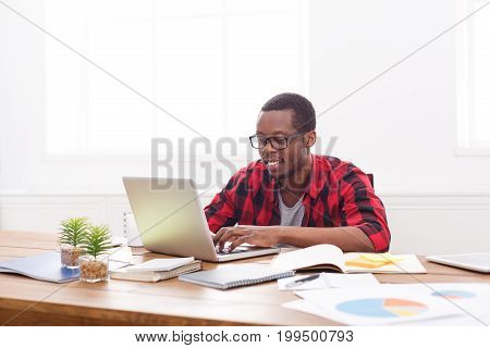 Happy black businessman in office, in casual, work with laptop in good spirits