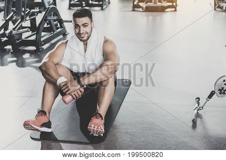 Portrait of man demonstrating happiness while having rest after good training in fitness center. He is sitting and holding bottle of water. Copy space