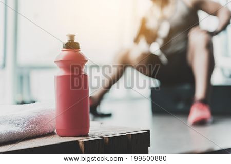 Focus on close up bottle with water situating on table in comfortable fitness center. Athlete engaging in sports