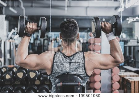 Man doing exercise with iron dumbbells for good back. He sitting on chair in comfortable keep-fit studio