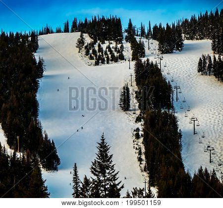 Skiers and snowboarders on Big Mountain as the shadows grow long.
