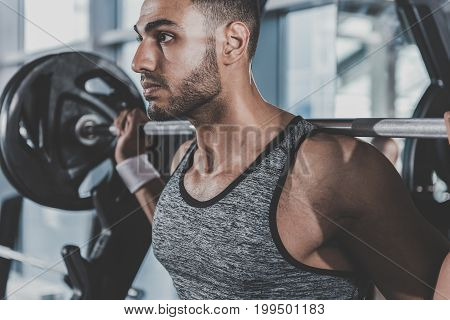 Side view profile serene bearded athlete pumping iron in keep-fit studio