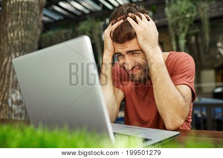 Outdoor portrait of tired overworked young businessman feeling stressed while facing a problem, doing accounts and calculating expenses by himself, squeezing his head. People and business.