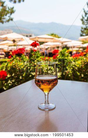 Glass of wine on a wooden table in the background of beach umbrellas in a mountain landscape