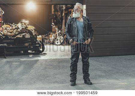 Serious aged bearded biker is putting hands in pockets and glancing aside. Different modern motorbikes are at garage. Portrait