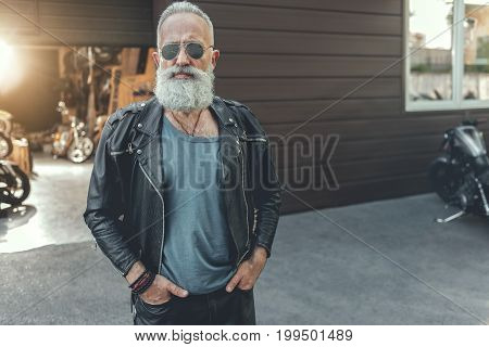 Severe aged biker in goggles is standing near open garage. He putting hands in pockets and glancing at camera. Portrait. Copy space