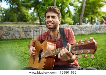 Outdoor portrait of joyfully singing songs with closed eyes bearded guitarist. Musician with darlk hair dressed casuslly playing guitar in the park.