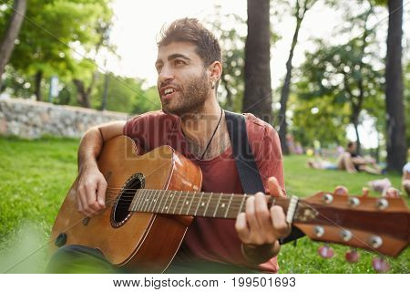Talented street musician playing his best song at the park. Stylish, good-looking man holding guotar in his hands and singing songs to people passing by.