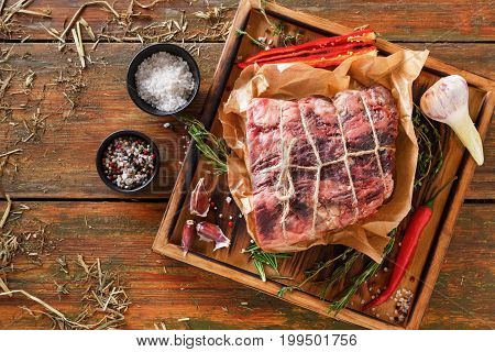 Raw black angus beef bound with rope in craft paper on cutting board. Aged prime marble meat, herbs and spices at rustic wood background, top view, copy space