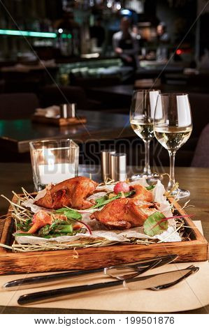 Romantic dinner at gourmet cuisine restaurant. Quails with asparagus and chanterelles served on grungy wooden platter, wine glasses and a candle on table. Exclusive meals for a foodie, copy space