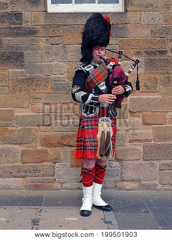 Scottish Piper from Edinburgh. Edinburgh, Scotland - July 27, 2017 Scottish piper in national dress playing on the street in Edinburgh.